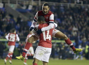 Photo -   Arsenal's Theo Walcott, front, and Francis Coquelin, top, celebrate after scoring during the English League Cup soccer match between Reading and Arsenal at Madejski Stadium in Reading, England, Tuesday, Oct. 30, 2012. (AP Photo/Kirsty Wigglesworth)