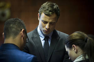 Photo - Oscar Pistorius cries as he prays with his sister Aimee and brother Carl in the magistrates court in Pretoria, South Africa, Monday, Aug. 19, 2013.  Pistorius was indicted Monday on charges of murder and illegal possession of ammunition for the shooting death of his girlfriend Reeva Steenkamp. (AP Photo)