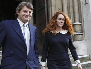 Photo -   FILE This Friday, May 11, 2012 file photo shows Rebekah Brooks, former chief executive of News International and her husband Charlie Brooks leaving the High Court in London after giving evidence to the Leveson Inquiry. Brooks said Tuesday May 15, 2012 she and her husband will face charges over Britain's tabloid phone hacking scandal. Brooks, 43, said Tuesday in a statement that she will be prosecuted over allegations of obstruction of justice. (AP Photo/Sang Tan)