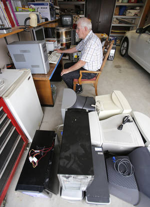 Photo - Dave Stewart works on a computer in his garage in Oklahoma City. Photo By Steve Gooch, The Oklahoman <strong>Steve Gooch - The Oklahoman</strong>