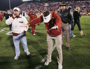 Photo - BOW: OU head coach Bob Stoops bows to fans as Regent Rick Dunning, left, looks on after the college football game between the University of Oklahoma Sooners and Texas Tech University at Gaylord Family -- Oklahoma Memorial Stadium in Norman, Okla., Saturday, Nov. 22, 2008. OU won, 65-21. BY NATE BILLINGS, THE OKLAHOMAN