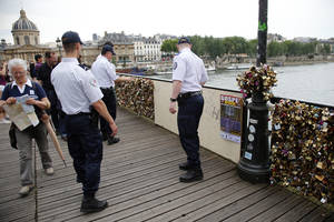 Photo - French police officers check out a wooden repaired section of the Pont des Arts bridge after a chunk of fencing with thousands of locks fell off under their weight in Paris, Monday, June 9, 2014. The thousands of locks that cling like barnacles to the Pont des Arts in Paris have become a symbol of danger, rather than love, after a chunk of fencing fell off under their weight. The fencing tumbled late Sunday on the pedestrian bridge, which crosses the Seine. (AP Photo/Francois Mori)