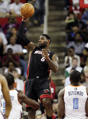 photo -   Miami Heat's LeBron James (6) saves the ball from going out of bounds as Charlotte Bobcats' DaJuan Summers and Bismack Biyombo (0) watch during the first half of an NBA preseason basketball game in Raleigh, N.C., Tuesday, Oct. 23, 2012. (AP Photo/Gerry Broome)
