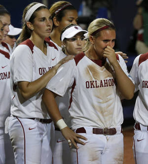 Photo - Oklahoma's Kelsey Stevens pats Shelby Pendley on the back after the tenth game of the Women's College World Series softball tournament where Oregon defeated Oklahoma 4-2 at ASA Hall of Fame Stadium on Saturday, May 31, 2014 in Oklahoma City, Okla.  Photo by Steve Sisney, The Oklahoman