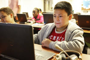 Photo - Erick Cifuentes, 12, from the Boys and Girls Club learns how to edit a video in a computer class at the OCU Intergenerational Computer Center on Monday. PHOTO BY DAVID MCDANIEL, THE OKLAHOMAN <strong>David McDaniel - The Oklahoman</strong>