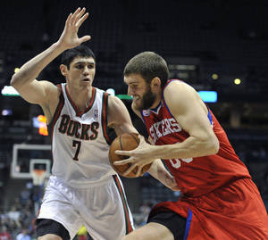Photo - Milwaukee Bucks' Ersan Ilyasova (7) defends as Philadelphia 76ers' Spencer Hawes drives to the basket during the first half of an NBA basketball game on Wednesday, Feb. 13, 2013, in Milwaukee. (AP Photo/Jim Prisching)