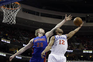 Photo - Philadelphia 76ers' Evan Turner (12) pulls in a rebound against Detroit Pistons' Kyle Singler (25) in the first half of an NBA basketball game, Monday, Dec. 10, 2012, in Philadelphia. (AP Photo/Matt Slocum)