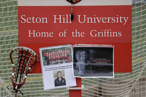 Photo - A lacrosse goal serves as a memorial for Seton Hill University's women's lacrosse coach Kristina Quigley on the school's  Greensburg, Pa. campus, Sunday, March 17, 2013. Coach Quigley and the tour bus driver were killed when a tour bus carrying three coaches and members of the Seton Hill women's lacrosse team crashed at about 9 a.m., Saturday morning on the Pennsylvania turnpike, spokeswoman Renee Colborn said. It's not clear what caused the crash, but state police were investigating, said Megan Silverstram of the Cumberland County public safety department. (AP Photo/Gene J. Puskar)