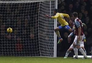 Photo - Arsenal's Theo Walcott, second right, scores his second goal against West Ham United during their English Premier League soccer match at Upton Park, London, Thursday, Dec. 26, 2013. (AP Photo/Sang Tan)