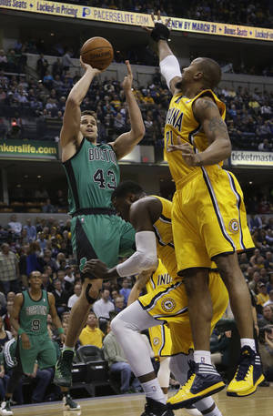 Photo - Boston Celtics center Kris Humphries (43) shoots over Indiana Pacers defenders David West (21) and Roy Hibbert during the first half of an NBA basketball game in Indianapolis, Tuesday, March 11, 2014. (AP Photo/AJ Mast)