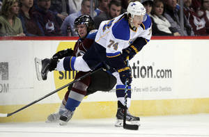 Photo - Colorado Avalanche defenseman Jan Hejda (8) checks St. Louis Blues right wing T.J. Oshie (74) during the first period of an NHL hockey game in Denver, Wednesday, Nov. 27, 2013. (AP Photo/Joe Mahoney)