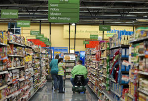 Photo - Customers shop at Wal-Mart Neighborhood Market in Bentonville, Ark., Thursday, June 5, 2014. Wal-Mart's supercenters still account for 80 percent of its 4,000-plus U.S. stores, but the retailer is opening smaller outlets that cater to shoppers looking for more convenience. It now plans to open 270 to 300 small stores during the current fiscal year — double its initial forecast. (AP Photo/Sarah Bentham)