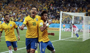 Photo - Brazil's Hernanes celebrates with Neymar, right, after Neymar scored his second goal on a penalty kick during the group A World Cup soccer match between Brazil and Croatia, the opening game of the tournament, in the Itaquerao Stadium in Sao Paulo, Brazil, Thursday, June 12, 2014.  Left is Brazil's Dani Alves. (AP Photo/Ivan Sekretarev)