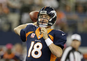 Photo - Denver Broncos quarterback Peyton Manning (18) passes with under two minutes to go during the fourth quarter of an NFL football game against the Dallas Cowboys Sunday, Oct. 6,2013, in Arlington, Texas. The Broncos won 51-48. (AP Photo/Tony Gutierrez)