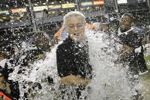 Photo - National team fullbacks J.C. Copeland, left, of LSU, and Ray Agnew, right, of Southern Illinois, dump water on coach Dick Vermeil as they celebrate the team's 31-17 win against the American team in the NFLPA Collegiate Bowl football game Saturday, Jan. 18, 2014, in Carson, Calif. (AP Photo/Jae C. Hong)