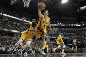 Photo - Indiana Pacers guard Lance Stephenson (1) and forward Luis Scola (4) go after a loose ball while playing the Los Angeles Lakers during the first half of an NBA basketball game in Indianapolis, Tuesday, Feb. 25, 2014. (AP Photo/AJ Mast)