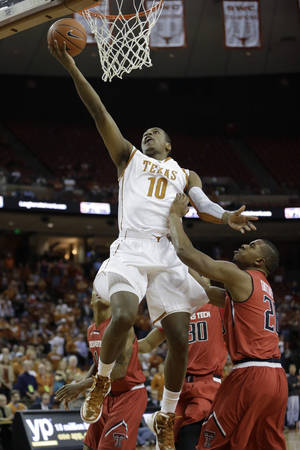 Photo - Texas' Jonathan Holmes (10) scores over Texas Tech's Toddrick Gotcher, right, during the first half of an NCAA college basketball game on Saturday,  Jan. 11, 2014, in Austin, Texas. (AP Photo/Eric Gay)