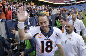 Photo - FILE - In this Dec. 22, 2013 file photo, Denver Broncos' Peyton Manning (18) waves to fans following an NFL football game against the Houston Texans in Houston. Manning threw his 51st touchdown pass of the season to set a new NFL record. Manning was the only unanimous choice for the 2013 Associated Press NFL All-Pro team Friday, Jan 3, 2014. It was his seventh time as a first-teamer, tying Hall of Famer Otto Graham for the most by a quarterback. (AP Photo/David J. Phillip)