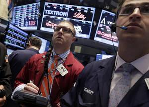 Photo - Trader Ryan Falvey, left, works on the floor of the New York Stock Exchange Friday, May 16, 2014. The stock market is little changed in early trading following sharp declines the previous day. (AP Photo/Richard Drew)