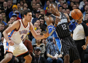 photo - Dwight Howard (12) of Orlando looks to get around the defense of Oklahoma City&#039;s Nick Collison (4) during the NBA basketball game between the Orlando Magic and Oklahoma City Thunder in Oklahoma City, Thursday, January 13, 2011. Photo by Nate Billings, The Oklahoman
