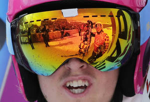 Photo - Canada's David Duncan, right, is reflected in the goggles of Sweden's John Eklund after their heat during men's ski cross competition at the Rosa Khutor Extreme Park, at the 2014 Winter Olympics, Thursday, Feb. 20, 2014, in Krasnaya Polyana, Russia. (AP Photo/Andy Wong)