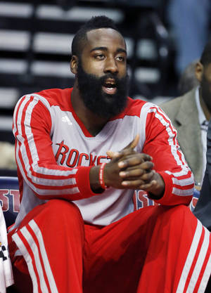 Photo - Houston Rockets guard James Harden watches from the bench during the first half of an NBA basketball game against the Detroit Pistons, Saturday, Dec. 21, 2013, in Auburn Hills, Mich. (AP Photo/Duane Burleson)