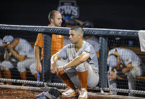 Photo - Texas shortstop C.J Hinojosa sits outside the dugout after Texas lost 4-3 to Vanderbilt in 10 innings in an NCAA baseball College World Series elimination game in Omaha, Neb., Saturday, June 21, 2014. Vanderbilt advanced to the championship series. (AP Photo/Eric Francis)