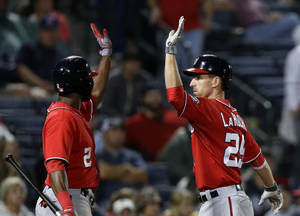 Photo - Washington Nationals' Adam LaRoche, right, is high-fived by teammate Denard Span after hitting a home run in the 15th inning of a baseball game against the Atlanta Braves, Sunday, Aug. 18, 2013, in Atlanta. (AP Photo/David Goldman)