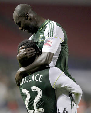 Photo - Portland Timbers defender Pa-Modou Kah, right, leaps into the arms of Timbers midfielder Rodney Wallace (22) for scoring against Chivas USA during the first half of an MLS soccer match on Saturday, Oct. 26, 2013, in Carson, Calif. (AP Photo/Alex Gallardo)