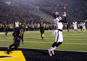 Photo - Texas A&M wide receiver Derel Walker, right, catches a 32-yard touchdown pass as Missouri safety Matt White (17) watches during the second quarter of an NCAA college football game on Saturday, Nov. 30, 2013, in Columbia, Mo. (AP Photo/L.G. Patterson)