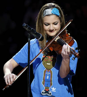 photo - Rae Grellner plays the national anthem on the violin before an NBA basketball game between the Oklahoma City Thunder and the Orlando Magic at Chesapeake Energy Arena in Oklahoma City, Friday, March 15, 2013. Grellner also plays for the Okarche High School girls basketball team. Photo by Nate Billings, The Oklahoman