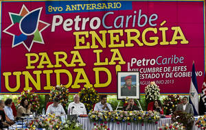 "Photo - Under a portrait of the late Hugo Chavez, Venezuela's President Nicolas Maduro, fourth from right, and Nicaragua's President Daniel Ortega, third from right,  preside over 8th Petrocaribe Summit in Managua, Nicaragua, Saturday, June 29, 2013. Venezuela created Petrocaribe in 2005 to sell fuel to member countries more cheaply and help finance their oil infrastructure projects.  Petrocaribe will ""shape the establishment of its economic zone"" during the summit,  Maduro said.(AP Photo/Esteban Felix)"
