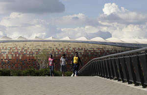 photo - Women walk over a bridge in front of Soccer City stadium, in Johannesburg, South Africa, Thursday, Jan. 17, 2013. The stadium will host the opening match of the African Cup of Nations on Saturday, Jan. 19. (AP Photo/Rebecca Blackwell)