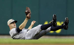 Photo - New York Yankees left fielder Brett Gardner slides after catching a fly by St. Louis Cardinals' Matt Holliday for an out during the first inning of a baseball game Monday, May 26, 2014, in St. Louis. (AP Photo/Jeff Roberson)