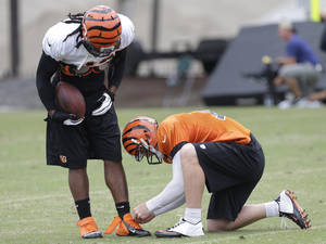 Photo - Cincinnati Bengals quarterback Andy Dalton, right, ties the shoes of running back BenJarvus Green-Ellis during practice at the NFL football team's training camp, Saturday, July 27, 2013, in Cincinnati.  (AP Photo/Al Behrman)