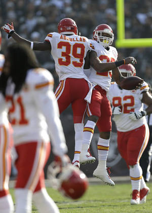 Photo - Kansas City Chiefs strong safety Eric Berry, top right, celebrates with defensive back Husain Abdullah (39) after returning an interception by Oakland Raiders quarterback Matt McGloin for a 47-yard touchdown during the first quarter of an NFL football game in Oakland, Calif., Sunday, Dec. 15, 2013. (AP Photo/Marcio Jose Sanchez)