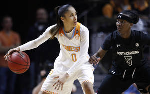 Photo - Tennessee guard Meighan Simmons (10) works against South Carolina guard Khadijah Sessions (5) in the second half of an NCAA college basketball game on Sunday, March 2, 2014, in Knoxville, Tenn. Tennessee won 73-61. (AP Photo/Wade Payne)