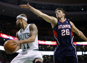 Photo - Atlanta Hawks guard Kyle Korver (26) defendsBoston Celtics guard Jerryd Bayless (11) during the first quarter of an NBA basketball game in Boston, Wednesday, Feb. 26, 2014. (AP Photo/Elise Amendola)