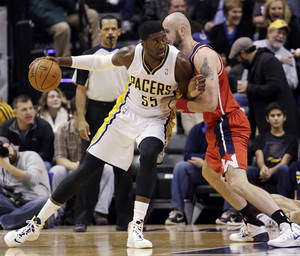 Photo - Indiana Pacers center Roy Hibbert, left, looks to go around Washington Wizards center Marcin Gortat, of Poland, during the first half of an NBA basketball game in Indianapolis, Friday, Jan. 10, 2014. (AP Photo/AJ Mast)