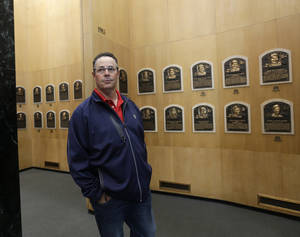 Photo - Former Atlanta Braves pitcher Greg Maddux walks through the Plaque Gallery during his orientation visit at the Baseball Hall of Fame on Monday, March 24, 2014, in Cooperstown, N.Y. Maddux will be inducted to the hall in July. (AP Photo/Mike Groll)