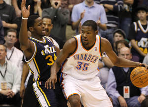 Photo - Utah Jazz forward C.J. Miles (34) guards Oklahoma City Thunder forward Kevin Durant (35) during the second half of an NBA basketball game Monday, Nov. 15, 2010, in Salt Lake City. The Thunder won 115-108. (AP Photo/Jim Urquhart) ORG XMIT: UTJU111