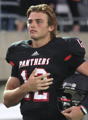 photo - HIGH SCHOOL FOOTBALL: Colleyville Heritage senior quarterback Cody Thomas (12) during the playing of the national anthem before the start of his team's game against Flower Mound at Pennington Field on Friday, September 14, 2012. (Kelley Chinn/Special Contributor)  ORG XMIT: DMN1209142151192011