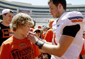 Photo - OKLAHOMA STATE UNIVERSITY / OSU / COLLEGE FOOTBALL: OSU's Wes Lunt signs the shirt of twelve-year-old Luke Fritzler of Enid after Oklahoma State's spring football game at Boone Pickens Stadium in Stillwater, Okla., Saturday, April 21, 2012. Photo by Bryan Terry, The Oklahoman
