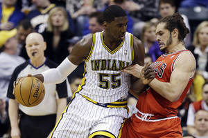Photo - Indiana Pacers' Roy Hibbert (55) is defended by Chicago Bulls' Joakim Noah during the first half of an NBA basketball game, Sunday, March 3, 2013, in Indianapolis. (AP Photo/Darron Cummings)