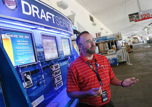 Photo - In this July 8, 2014, photo, Pete Spike, general manager for Delaware North  Companies Sportservice, talks about the newly launched self-service beer kiosks at Target Field, home of the Minnesota Twins and the upcoming All-Star game, in Minneapolis. (AP Photo/Jim Mone)