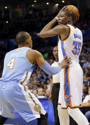 Photo - Oklahoma City's Kevin Durant (35) keeps the ball away from Denver's Randy Foye (4) during an NBA basketball game between the Oklahoma City Thunder and the Denver Nuggets at the Chesapeake Energy Arena in Oklahoma City, Monday, March 24, 2014. Photo by Nate Billings, The Oklahoman