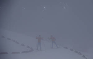 Photo - Unidentified athletes ski through the fog as  the men's biathlon 15K mass start race has been postponed due to the lack of visibility at the 2014 Winter Olympics, Sunday, Feb. 16, 2014, in Krasnaya Polyana, Russia. (AP Photo/Gregorio Borgia)