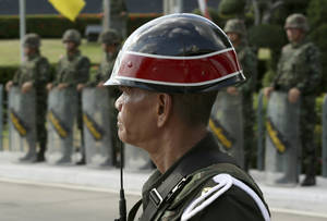 Photo - A Thai military police officer stands next to a line of soldiers standing guard outside the Army Club in Bangkok, Thailand Wednesday, May 21, 2014. Thailand's army chief Gen. Prayuth Chan-Ocha assumed the role of mediator Wednesday by summoning the country's key political rivals for face-to-face talks one day after imposing martial law. The meeting ended without any resolution, however, underscoring the profound challenge the army faces in trying to end the country's crisis. (AP Photo/Apichart Weerawong)