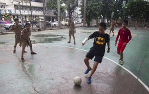 Photo - Thai students play soccer under an expressway in Bangkok, Thailand, Thursday, June 12, 2014. The junta that overthrew Thailand's elected government has struck a blow for freedom — the freedom to watch soccer. On Thursday, the National Broadcasting and Telecoms Commission announced it had struck a 427 million baht ($13 million) compensation deal with RS so the entire World Cup can be shown on free channels. (AP Photo/Sakchai Lalit)