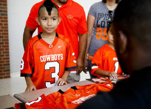 "Photo - Dominik Villanueva, 9 of Clinton, gets a jersey autographed by Oklahoma State football players August 3, 2013 at Gallagher-Iba Arena for fan appreciation day. Dominik said meeting his favorite player Clint Chelf was ""unexplainable.""  KT King, For The Oklahoman"